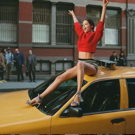 Lima posing for photo her in a yellow car